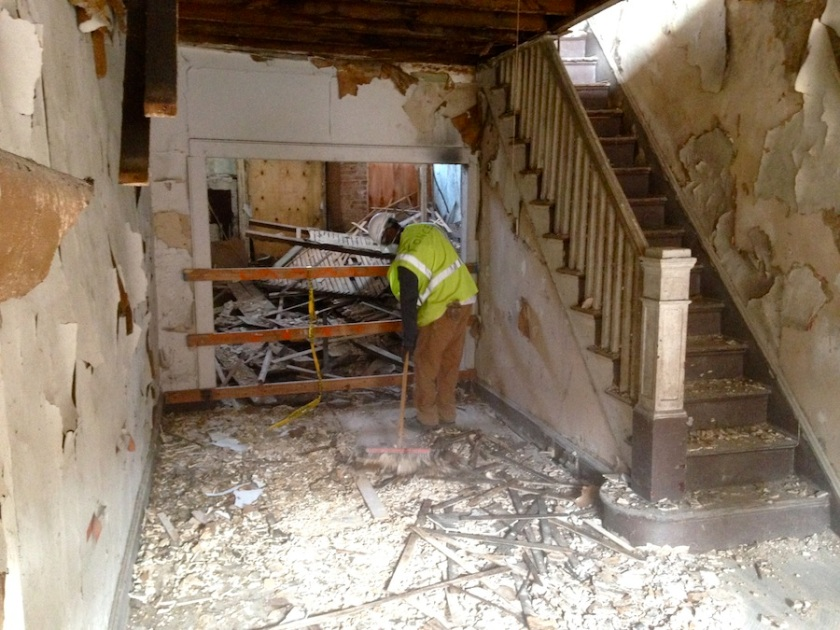 Ron sweeps up bits of wallpaper, lath and plaster that inevitable accrue during any decon project.